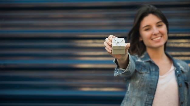 Femme souriante avec boite présente Photo gratuit