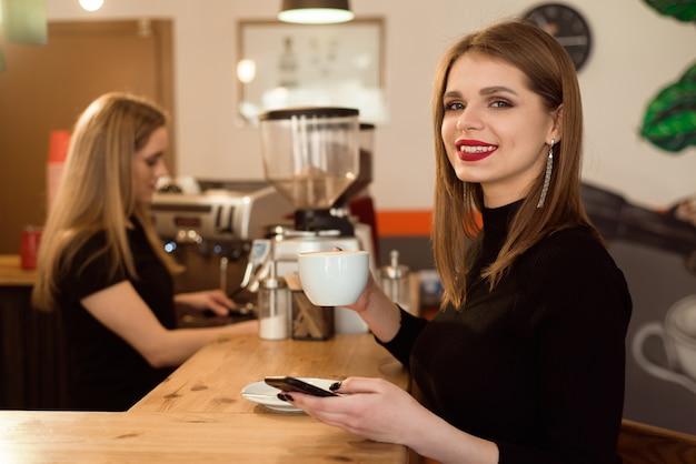 Femme souriante de bonne humeur profiter d'une tasse de café assis dans un café. Photo Premium