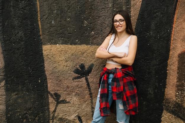 Femme souriante avec les bras croisés debout devant le mur Photo gratuit