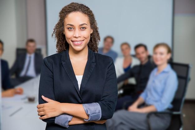 Femme souriante avec les bras croisés et ses collègues de mise au point Photo gratuit