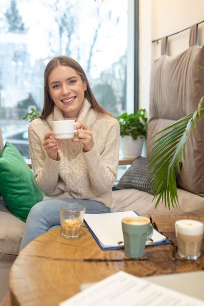 Une Femme Souriante Buvant Beaucoup De Café Tout En Travaillant Photo Premium
