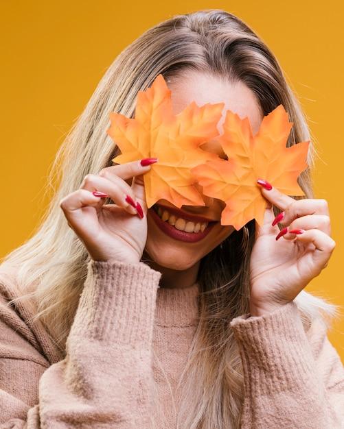 Femme souriante cachant ses yeux avec des feuilles d'érable sur fond jaune Photo gratuit
