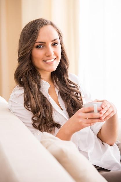Femme souriante avec café sur canapé Photo Premium