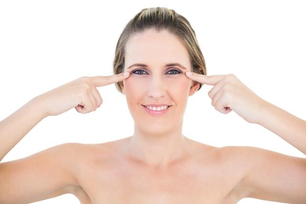 Femme souriante à la caméra montrant des rides sur ses yeux Photo Premium