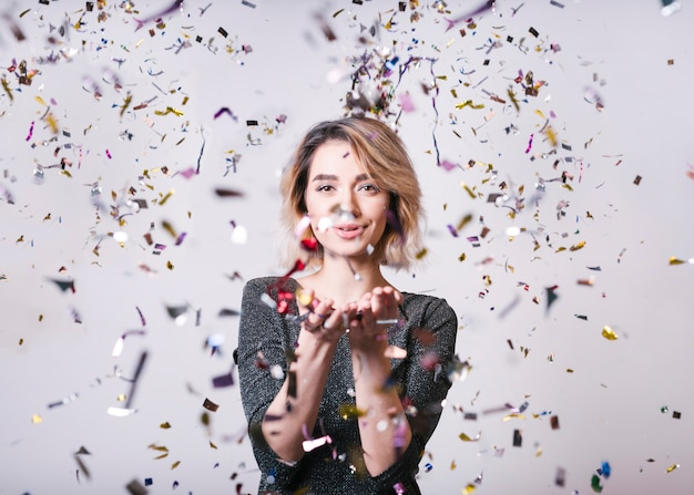 Femme souriante avec des confettis volants à la fête Photo gratuit
