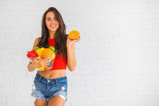 Femme souriante debout contre le mur tenant des légumes frais et des fruits Photo gratuit