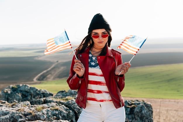 Femme souriante avec des drapeaux américains posant au sommet de la montagne Photo gratuit