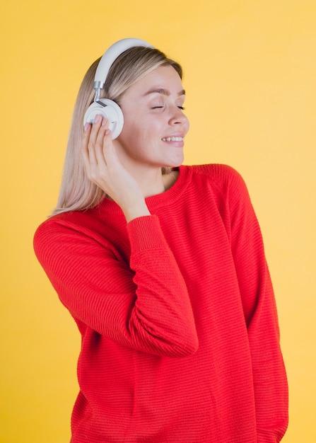 Femme souriante écoutant de la musique Photo gratuit