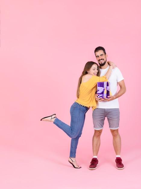 Femme souriante, étreindre, elle, petit ami, tenue, boîte cadeau, contre, rose, toile de fond Photo gratuit