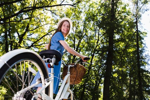 Femme souriante à faible angle avec vélo Photo gratuit