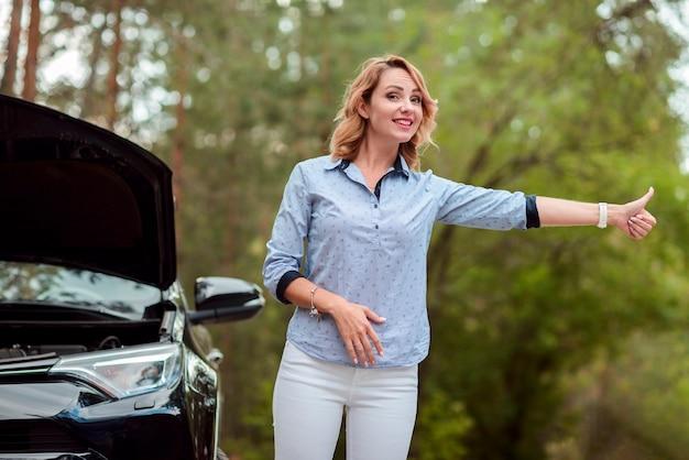 Femme souriante faisant de l'auto-stop Photo gratuit