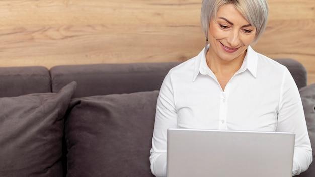 Femme souriante haute angle travaillant sur un ordinateur portable Photo gratuit