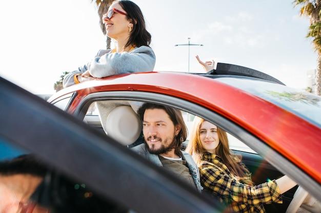Femme souriante et homme positif assis dans la voiture près de dame se penchant de l'auto Photo gratuit