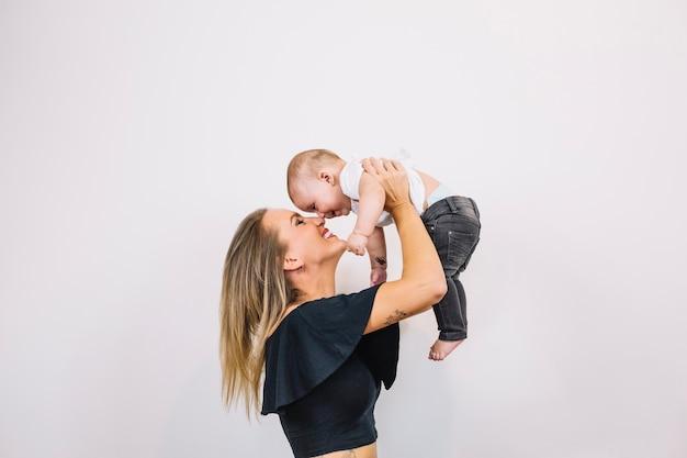 Femme souriante jouant avec bébé Photo gratuit