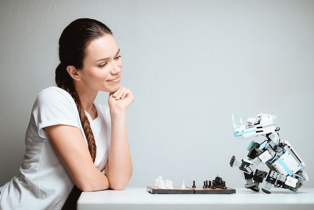 Femme souriante et joue aux échecs avec un robot. Photo Premium
