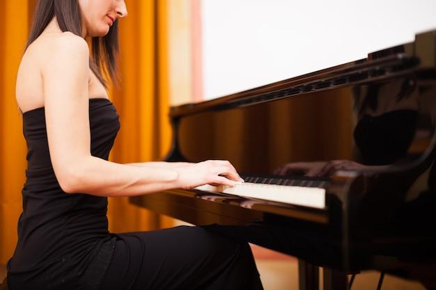 Femme souriante, jouer piano Photo Premium