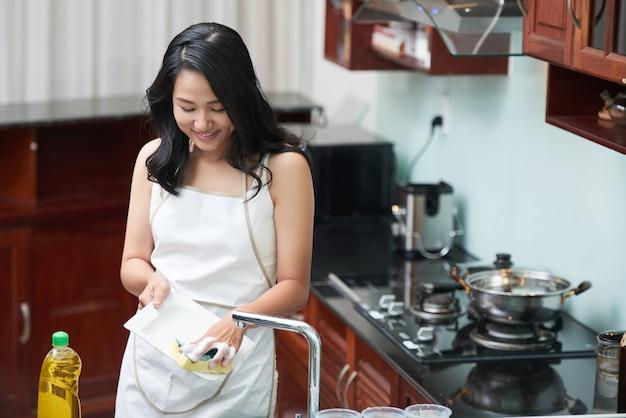 Femme souriante, laver la vaisselle Photo gratuit
