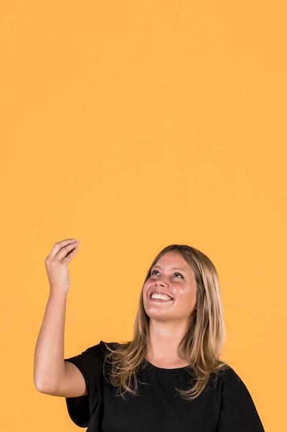 Femme souriante levant et gesticulant sur fond de mur jaune Photo gratuit