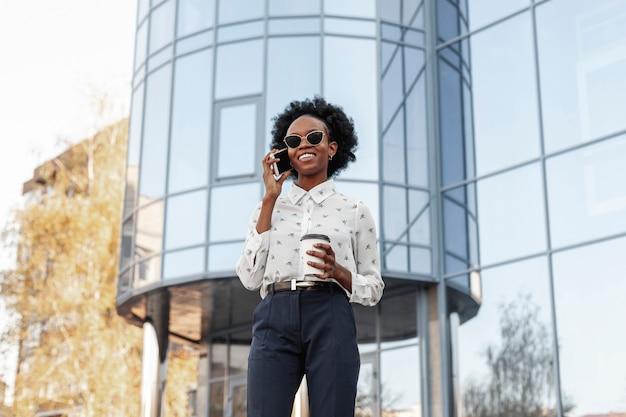Femme souriante avec des lunettes de soleil parlant au téléphone Photo gratuit