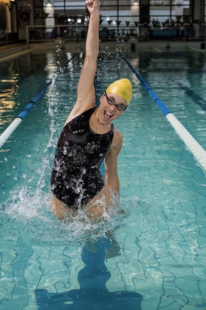 Femme souriante en maillot de bain sautant dans la piscine Photo Premium