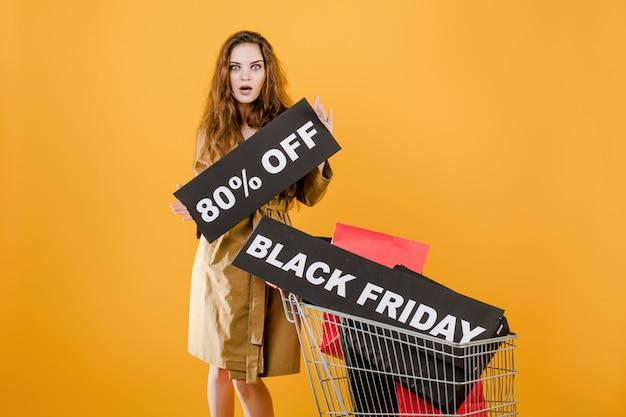 Femme souriante en manteau d'automne avec signe vendredi noir 80% et sacs colorés dans le panier isolé sur jaune Photo Premium