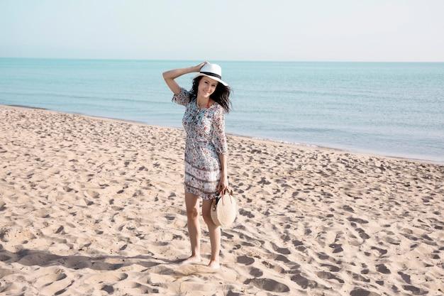 Femme souriante marchant au bord de la mer Photo gratuit