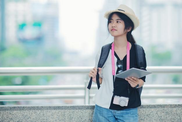 Femme souriante marchant en plein air, jeune femme admirant le paysage urbain avec allée et bâtiments en arrière-plan. Photo gratuit