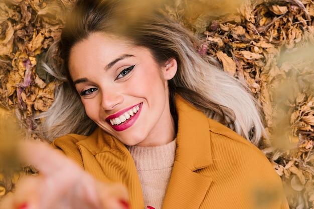 Femme souriante moderne, regardant la caméra se trouvant sur des feuilles sèches pendant la saison d'automne Photo gratuit