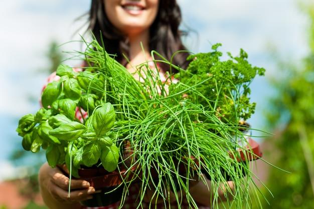 Femme souriante montrant des herbes en pot à la caméra Photo Premium