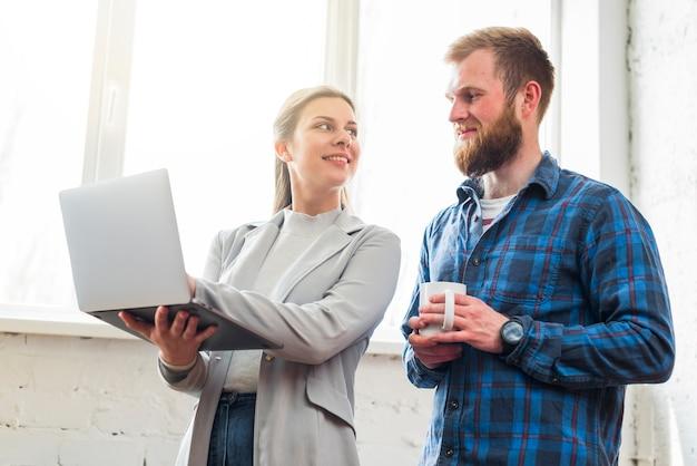 Femme souriante, montrant un ordinateur portable à son collègue au lieu de travail Photo gratuit