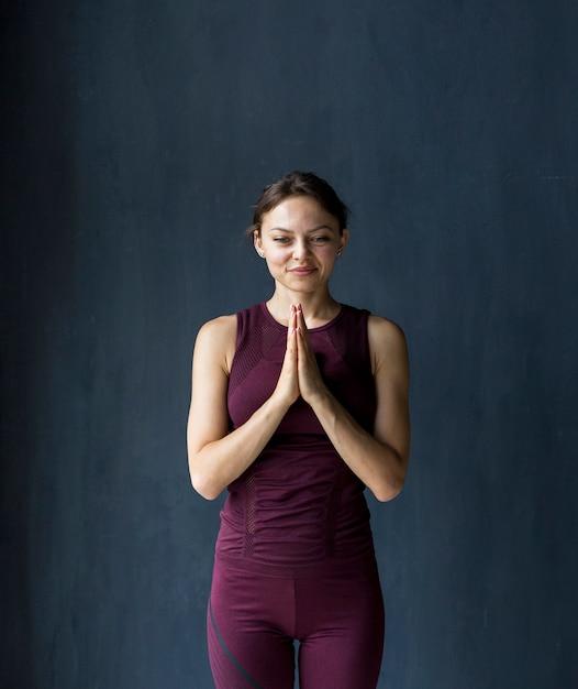 Femme souriante montrant sa gratitude dans une pose de namaste Photo gratuit