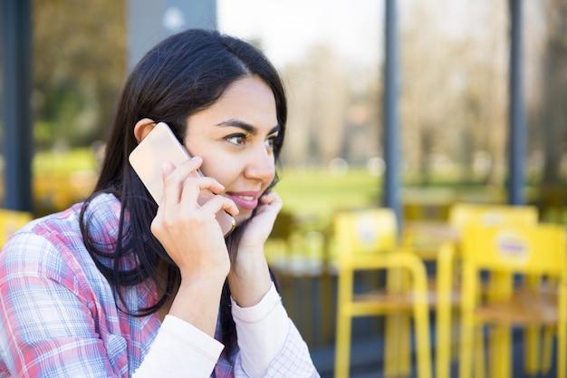 Femme souriante, parler au téléphone portable au café en plein air Photo gratuit