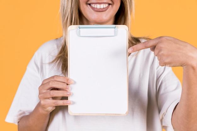 Femme souriante, pointant le doigt sur du papier blanc vierge sur le presse-papiers Photo gratuit