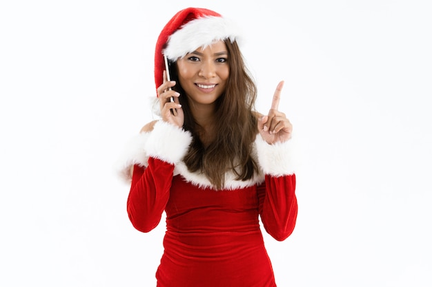 Femme souriante portant un costume de noël et pointant vers le haut Photo gratuit