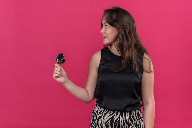Femme Souriante Portant Maillot Noir Tenant Une Carte Bancaire Et Regarder à Côté Sur Le Mur Rose Photo gratuit