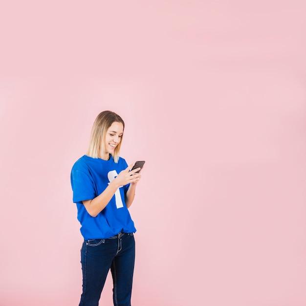 Femme souriante portant le t-shirt de facebook à l'aide de téléphone portable Photo gratuit