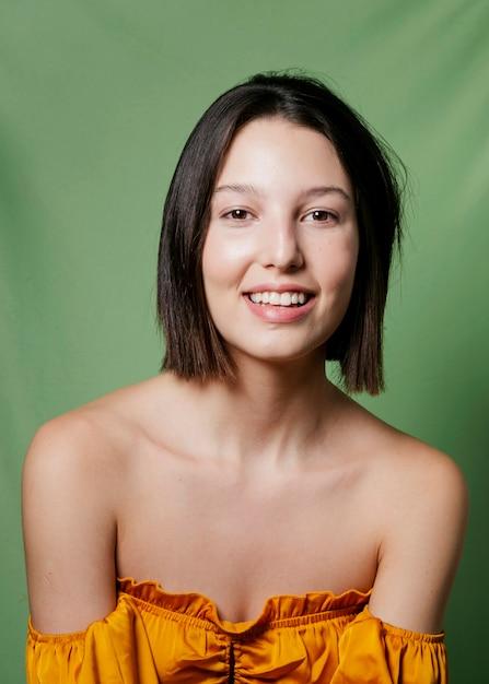 Femme souriante posant en haut jaune Photo gratuit
