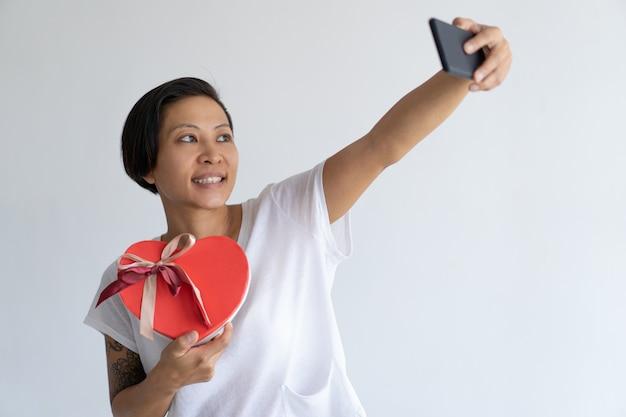 Femme souriante prenant une photo de selfie avec une boîte cadeau en forme de coeur Photo gratuit
