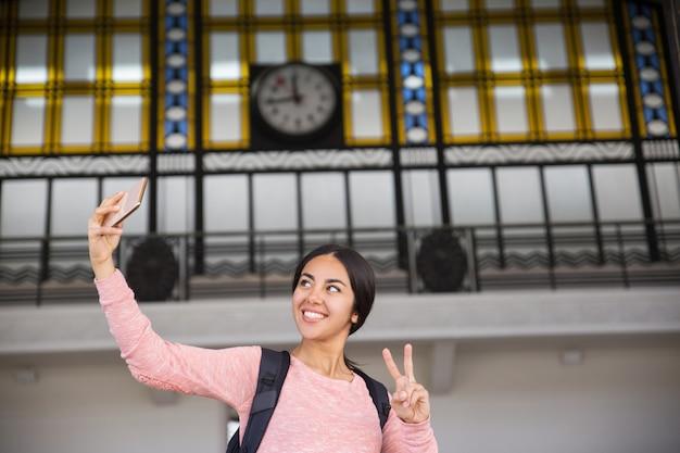 Femme souriante prenant une photo de selfie et montrant le signe de la victoire Photo gratuit