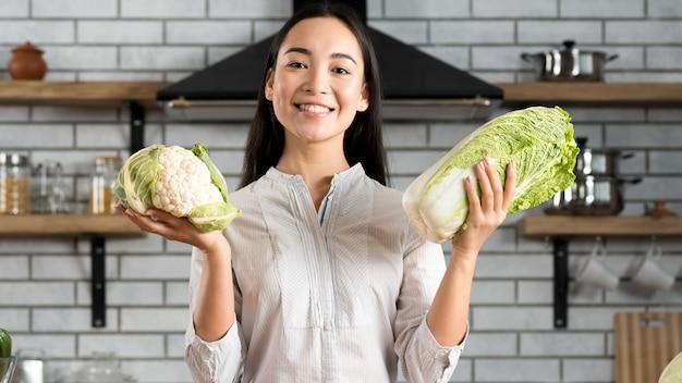 Femme souriante, projection, frais, chou-fleur vert, et, laitue, dans cuisine Photo gratuit