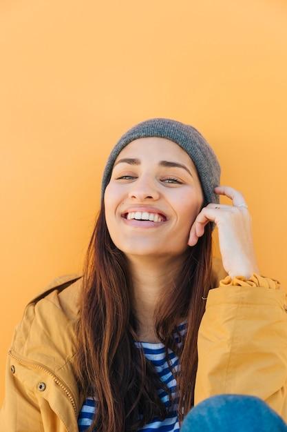 Femme souriante regardant la caméra assis devant la surface jaune Photo gratuit
