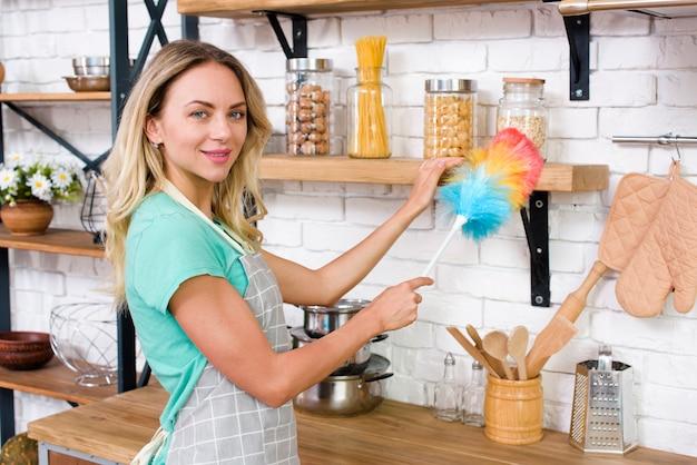 Femme souriante regardant la caméra en époussetant dans la cuisine Photo gratuit
