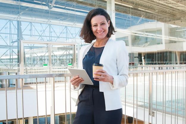 Femme souriante regardant la caméra, tenant une tablette, café à emporter Photo gratuit