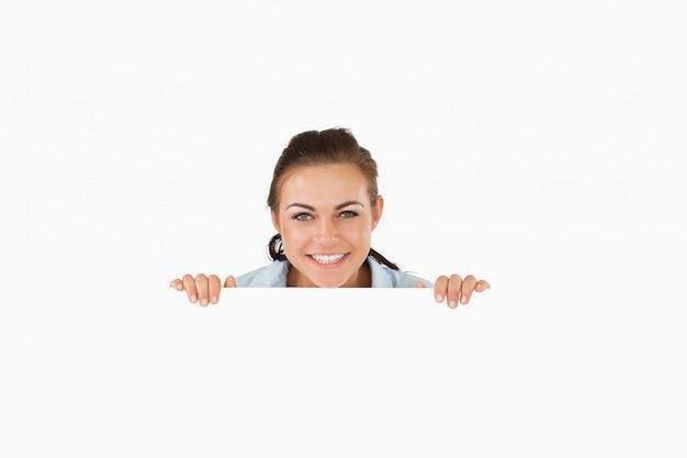 Femme souriante regardant par-dessus le mur Photo Premium