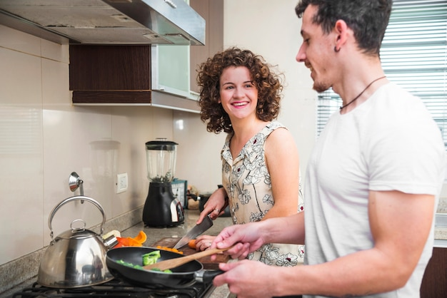 Femme souriante regardant son mari préparant un repas dans la cuisine Photo gratuit