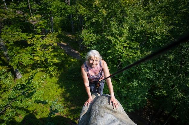 Femme souriante, le rockclimber atteint le sommet du rocher. matériel d'escalade Photo Premium