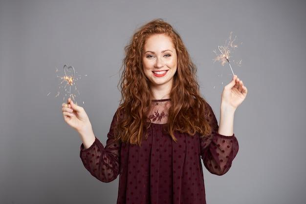 Femme Souriante S'amusant Avec Des Cierges Magiques Photo gratuit