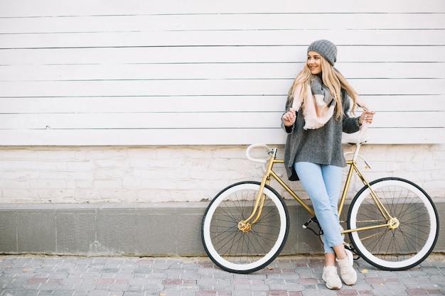 Femme souriante s'appuyant sur bicyclette près du mur Photo gratuit