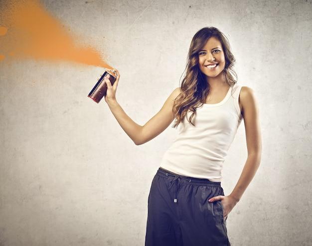 Femme souriante avec un spray de peinture Photo Premium