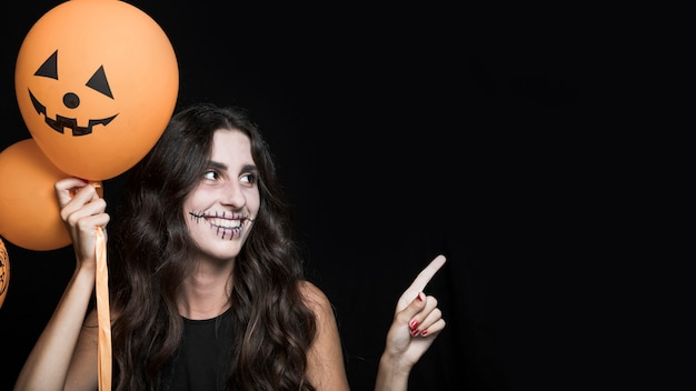 Femme souriante tenant des ballons d'halloween Photo gratuit